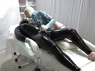 The latex doctor is playing with the patient's penis
