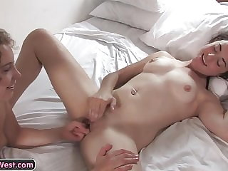 Petite lesbian amateurs fingering their pussies on the bed